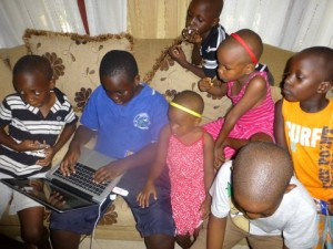 The child with the computer has his young relatives fascinated.